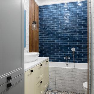 На фото: ванная комната в современном стиле с желтыми фасадами, ванной в нише, душем над ванной, синей плиткой, настольной раковиной, разноцветным полом и белой столешницей с