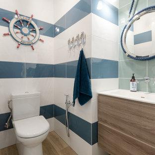Идея дизайна: ванная комната в морском стиле с плоскими фасадами, светлыми деревянными фасадами, раздельным унитазом, синей плиткой, белой плиткой, паркетным полом среднего тона, монолитной раковиной, коричневым полом, белой столешницей, тумбой под одну раковину и подвесной тумбой