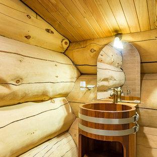 Modelo de cuarto de baño rústico, grande, con paredes beige, suelo de madera pintada, lavabo con pedestal y puertas de armario de madera oscura