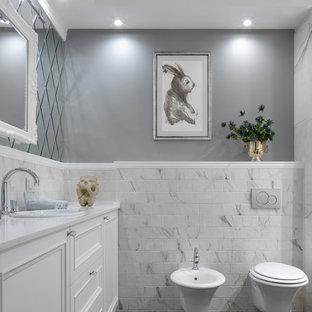 Свежая идея для дизайна: ванная комната в стиле современная классика с фасадами с утопленной филенкой, белыми фасадами, инсталляцией, белой плиткой, серыми стенами, накладной раковиной, серым полом и белой столешницей - отличное фото интерьера