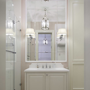 Immagine di una piccola stanza da bagno con doccia classica con doccia alcova, top in superficie solida, porta doccia a battente, ante con bugna sagomata, ante bianche, lavabo sottopiano, pavimento beige e pareti rosa