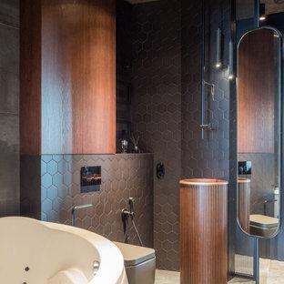 Bild på ett mellanstort funkis en-suite badrum, med släta luckor, skåp i mellenmörkt trä, ett hörnbadkar, våtrum, en vägghängd toalettstol, svart kakel, keramikplattor, grå väggar, klinkergolv i porslin, grått golv och dusch med gångjärnsdörr