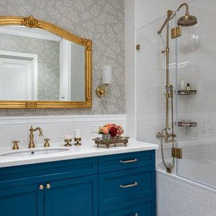 Стильный дизайн: главная ванная комната в классическом стиле с серыми стенами, разноцветным полом, обоями на стенах, фасадами с утопленной филенкой, синими фасадами, врезной раковиной, белой столешницей, тумбой под одну раковину и напольной тумбой - последний тренд