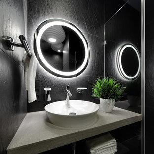 Свежая идея для дизайна: ванная комната среднего размера в современном стиле с душевой кабиной, черными фасадами, инсталляцией, черной плиткой, керамогранитной плиткой, черными стенами, раковиной с пьедесталом, столешницей из искусственного камня, черным полом, серой столешницей и полом из керамической плитки - отличное фото интерьера