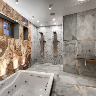 Новый формат декора квартиры: огромная баня и сауна в современном стиле с гидромассажной ванной, разноцветной плиткой, плиткой из листового камня, разноцветными стенами, полом из керамогранита, серым полом, открытым душем, двойным душем, настольной раковиной, столешницей из дерева и коричневой столешницей