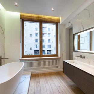 Выдающиеся фото от архитекторов и дизайнеров интерьера: главная ванная комната в современном стиле с плоскими фасадами, отдельно стоящей ванной, белыми стенами и монолитной раковиной