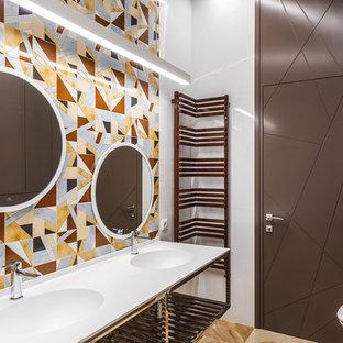 Новый формат декора квартиры: ванная комната в современном стиле с писсуаром, разноцветной плиткой, белыми стенами, монолитной раковиной, коричневым полом и белой столешницей