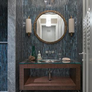 Новые идеи обустройства дома: ванная комната в современном стиле с открытыми фасадами, темными деревянными фасадами, синей плиткой, врезной раковиной и стеклянной столешницей