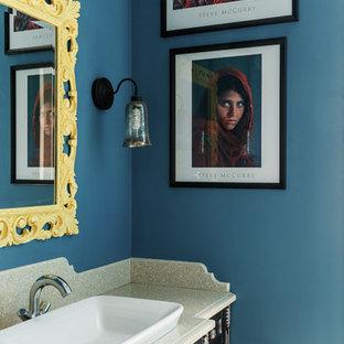 Пример оригинального дизайна: ванная комната в стиле фьюжн с фасадами с выступающей филенкой, темными деревянными фасадами, синими стенами и накладной раковиной