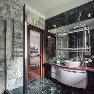Diseño de cuarto de baño con ducha, contemporáneo, de tamaño medio, con armarios con paneles lisos, puertas de armario blancas, ducha a ras de suelo, sanitario de pared, baldosas y/o azulejos verdes, baldosas y/o azulejos de mármol, paredes verdes, suelo de mármol, lavabo encastrado, encimera de madera, suelo verde, ducha con puerta corredera y encimeras marrones