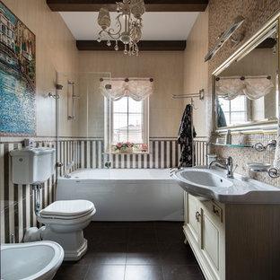 Пример оригинального дизайна интерьера: главная ванная комната в классическом стиле с бежевыми фасадами, ванной в нише, раздельным унитазом, бежевой плиткой, монолитной раковиной и коричневым полом