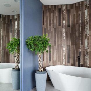 На фото: главные ванные комнаты в современном стиле с отдельно стоящей ванной, коричневой плиткой, серым полом и бетонным полом