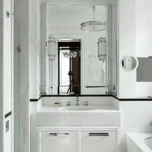 Пример оригинального дизайна интерьера: главная ванная комната в стиле современная классика с фасадами с декоративным кантом, белыми фасадами, ванной в нише, белой плиткой, врезной раковиной и белым полом