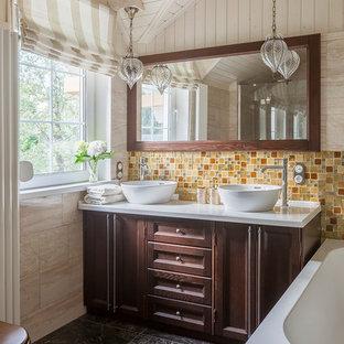 Идея дизайна: главная ванная комната среднего размера в стиле современная классика с фасадами с утопленной филенкой, темными деревянными фасадами, раздельным унитазом, бежевой плиткой, желтой плиткой, оранжевой плиткой, плиткой из травертина, бежевыми стенами, полом из керамической плитки, столешницей из искусственного камня, коричневым полом, белой столешницей, настольной раковиной и накладной ванной