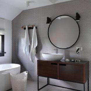 Стильный дизайн: главная ванная комната среднего размера в современном стиле с отдельно стоящей ванной, керамической плиткой, полом из керамогранита, настольной раковиной, столешницей из дерева, серым полом, плоскими фасадами, темными деревянными фасадами, белыми стенами, черно-белой плиткой и коричневой столешницей - последний тренд