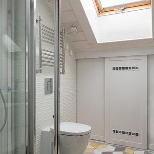 Foto de cuarto de baño con ducha, escandinavo, de tamaño medio, con sanitario de dos piezas, baldosas y/o azulejos blancos y suelo amarillo