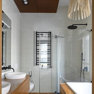 Стильный дизайн: ванная комната в современном стиле с плоскими фасадами, фасадами цвета дерева среднего тона, накладной ванной, угловым душем, белой плиткой, белыми стенами, паркетным полом среднего тона, настольной раковиной, столешницей из дерева, коричневым полом, душем с распашными дверями и коричневой столешницей - последний тренд