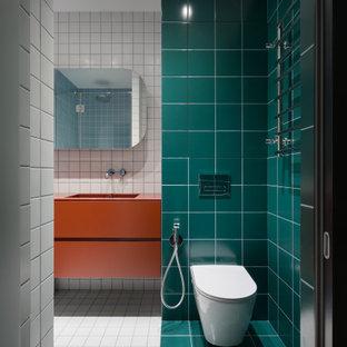 Bild på ett mellanstort funkis orange oranget badrum med dusch, med släta luckor, orange skåp, en vägghängd toalettstol, grön kakel, ett undermonterad handfat, vitt golv, en dusch i en alkov, keramikplattor, klinkergolv i keramik, bänkskiva i akrylsten och dusch med gångjärnsdörr
