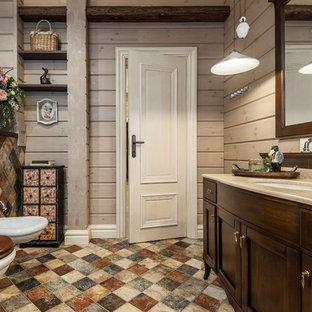 На фото: главная ванная комната среднего размера в стиле кантри с бежевыми стенами, разноцветным полом, фасадами в стиле шейкер, темными деревянными фасадами, врезной раковиной, бежевой столешницей, инсталляцией, разноцветной плиткой, керамической плиткой, полом из керамической плитки, столешницей из искусственного камня, ванной на ножках, угловым душем, душем с распашными дверями, унитазом, тумбой под одну раковину, напольной тумбой, балками на потолке и деревянными стенами