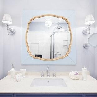 Immagine di una stanza da bagno tradizionale con ante con bugna sagomata, ante viola, pareti viola, lavabo sottopiano e top in marmo