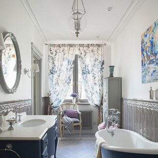 Пример оригинального дизайна: главная ванная комната в классическом стиле с синими фасадами, ванной на ножках, белыми стенами, полом из керамической плитки, врезной раковиной, мраморной столешницей, фасадами островного типа и разноцветным полом