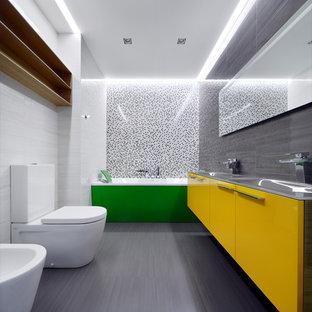 Foto di una stanza da bagno per bambini design di medie dimensioni con ante lisce, vasca ad alcova, pavimento con piastrelle in ceramica, top in vetro, piastrelle bianche, ante arancioni, bidè, piastrelle in ceramica, pareti marroni e lavabo rettangolare