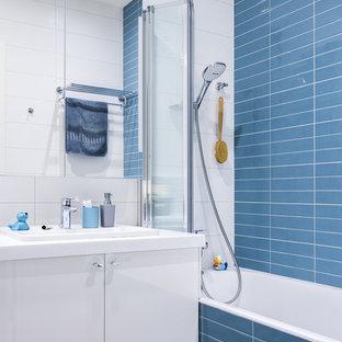 На фото: со средним бюджетом детские ванные комнаты среднего размера в современном стиле с плоскими фасадами, белыми фасадами, керамической плиткой, накладной раковиной, столешницей из искусственного кварца, ванной в нише, душем над ванной, синей плиткой и белой плиткой