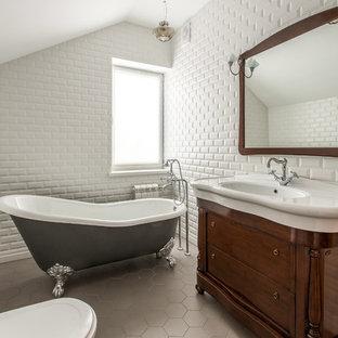 Стильный дизайн: главная ванная комната среднего размера в классическом стиле с темными деревянными фасадами, ванной на ножках, белой плиткой, белыми стенами, полом из керамогранита, серым полом, фасадами с утопленной филенкой, плиткой кабанчик и монолитной раковиной - последний тренд