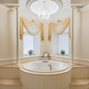 Immagine di una stanza da bagno vittoriana con vasca da incasso, piastrelle beige, pareti beige, pavimento beige e top beige