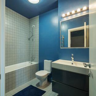 На фото: главные ванные комнаты в современном стиле с плоскими фасадами, черными фасадами, ванной в нише, душем над ванной, раздельным унитазом, белой плиткой, синими стенами и монолитной раковиной