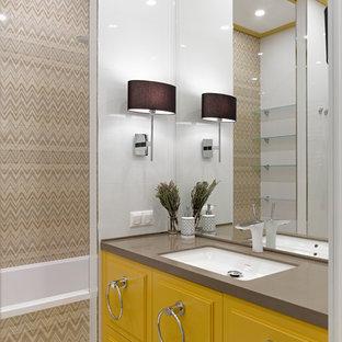 Idee per una stanza da bagno design con lavabo sottopiano, ante gialle, vasca/doccia, piastrelle beige, vasca da incasso e top grigio