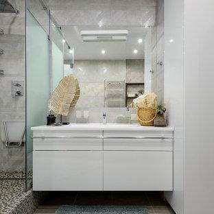 Новые идеи обустройства дома: большая главная ванная комната в современном стиле с плоскими фасадами, белыми фасадами, угловым душем, серой плиткой, керамической плиткой, серыми стенами, полом из керамической плитки, врезной раковиной, столешницей из искусственного камня, серым полом, душем с распашными дверями и белой столешницей