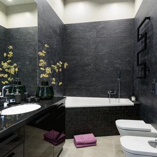 Источник вдохновения для домашнего уюта: большая главная ванная комната в современном стиле с плоскими фасадами, черными фасадами, ванной в нише, инсталляцией, черной плиткой, керамической плиткой, черными стенами, полом из керамической плитки, врезной раковиной, столешницей из искусственного камня, серым полом и черной столешницей