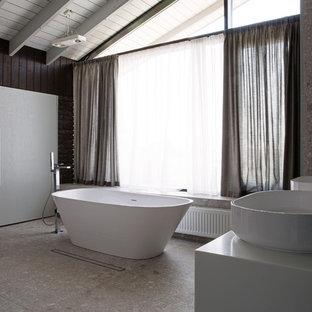 Cette image montre une très grand salle de bain principale design avec une baignoire indépendante, un placard avec porte à panneau surélevé, des portes de placard grises, un espace douche bain, un urinoir, un carrelage marron, des carreaux en terre cuite, un mur gris, un sol en marbre, un lavabo de ferme, un plan de toilette en surface solide, un sol gris et une cabine de douche à porte coulissante.