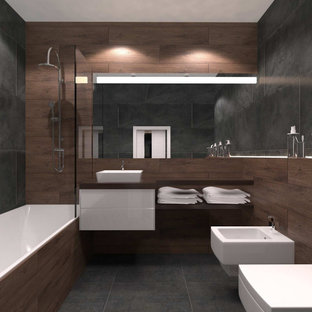 Design ideas for a mid-sized contemporary master bathroom in Other with flat-panel cabinets, white cabinets, an alcove tub, a shower/bathtub combo, a wall-mount toilet, black tile, porcelain tile, brown walls, porcelain floors, a wall-mount sink, granite benchtops, grey floor, a sliding shower screen, brown benchtops, an enclosed toilet, a double vanity, a floating vanity, panelled walls and recessed.