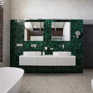 Aménagement d'une très grand salle de bain principale contemporaine avec un mur gris, une vasque, un placard à porte plane, des portes de placard grises, une baignoire sur pieds, un espace douche bain, un urinoir, un carrelage vert, des carreaux en terre cuite, un sol en carreau de terre cuite, un plan de toilette en surface solide, un sol gris et une cabine de douche à porte coulissante.