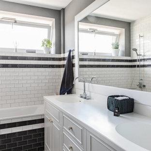 Пример оригинального дизайна: ванная комната среднего размера в стиле современная классика с белыми фасадами, ванной в нише, душевой кабиной, белой столешницей, керамической плиткой, тумбой под две раковины, встроенной тумбой, фасадами с утопленной филенкой, душем над ванной, черно-белой плиткой, серыми стенами, монолитной раковиной и открытым душем