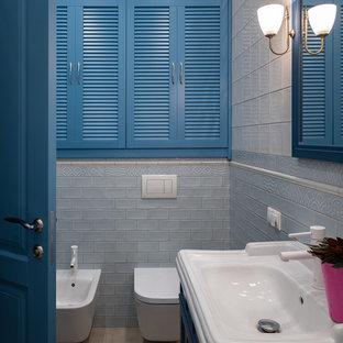 На фото: маленькая главная ванная комната в стиле неоклассика (современная классика) с фасадами с утопленной филенкой, синими фасадами, белой плиткой, керамической плиткой, полом из керамогранита, биде, монолитной раковиной и тумбой под одну раковину с