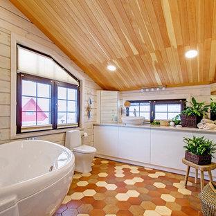 Esempio di una stanza da bagno padronale design con ante lisce, ante bianche, vasca freestanding, WC a due pezzi, pareti beige, pavimento con piastrelle a mosaico, lavabo a bacinella, pavimento arancione e top beige