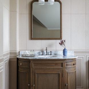 Idee per una stanza da bagno chic con ante con riquadro incassato, piastrelle beige, lavabo sottopiano, top in marmo, pavimento beige e ante in legno bruno