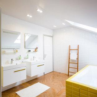 Стильный дизайн: ванная комната в современном стиле с белыми стенами, паркетным полом среднего тона, коричневым полом, плоскими фасадами, белыми фасадами, накладной ванной, белой плиткой, желтой плиткой, плиткой кабанчик и консольной раковиной - последний тренд