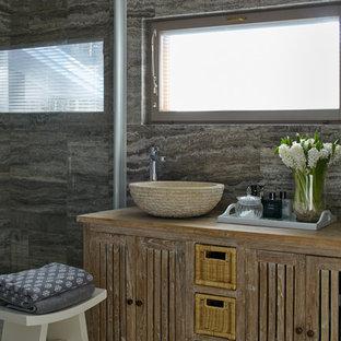 Создайте стильный интерьер: ванная комната в стиле рустика с искусственно-состаренными фасадами, серой плиткой, душевой кабиной, настольной раковиной и столешницей из дерева - последний тренд