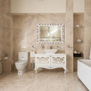 На фото: большая главная ванная комната в классическом стиле с бежевой плиткой, керамогранитной плиткой, полом из керамогранита, бежевым полом, белой столешницей, белыми фасадами и настольной раковиной