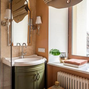 Идея дизайна: ванная комната в классическом стиле с фасадами с утопленной филенкой, зелеными фасадами, коричневой плиткой, оранжевыми стенами, монолитной раковиной и белой столешницей