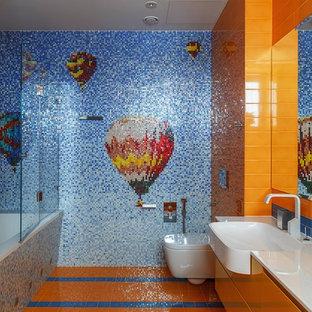 Immagine di una stanza da bagno per bambini eclettica di medie dimensioni con ante lisce, ante arancioni, vasca sottopiano e lavabo integrato