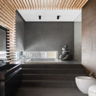 Ejemplo de cuarto de baño principal, rústico, con armarios con paneles lisos, puertas de armario negras, bañera japonesa, sanitario de pared, baldosas y/o azulejos marrones, baldosas y/o azulejos grises, lavabo sobreencimera y suelo gris