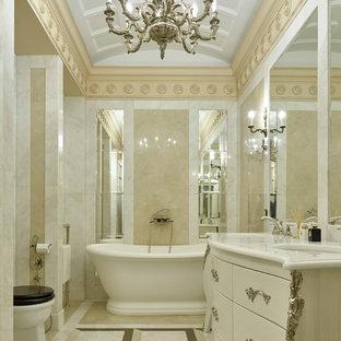 Стильный дизайн: главная ванная комната в классическом стиле с бежевой плиткой, белой плиткой, врезной раковиной, фасадами островного типа, отдельно стоящей ванной и разноцветным полом - последний тренд
