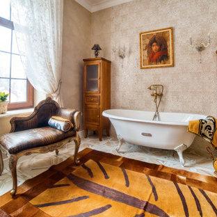Неиссякаемый источник вдохновения для домашнего уюта: большая главная ванная комната в викторианском стиле с ванной на ножках, бежевой плиткой, керамогранитной плиткой, полом из керамогранита и бежевым полом
