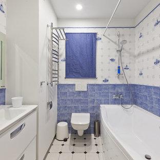 На фото: ванная комната среднего размера в морском стиле с душем над ванной, инсталляцией, керамической плиткой, белыми стенами, полом из керамогранита, плоскими фасадами, белыми фасадами, ванной в нише, синей плиткой, белой плиткой, монолитной раковиной и шторкой для душа с
