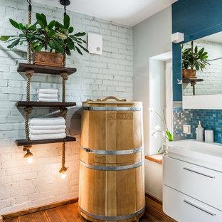 На фото: ванная комната в современном стиле с плоскими фасадами, белыми фасадами, синей плиткой, темным паркетным полом, коричневым полом, белыми стенами и монолитной раковиной с